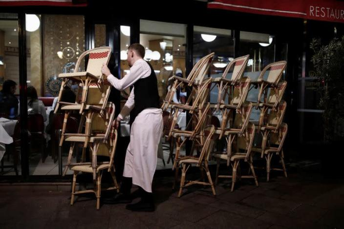 A restaurant employee clears out all the outside seats and prepares the closure of the place, as France's Prime Minister announced to close most all non-indispensable locations from midnight on Saturday, in Paris