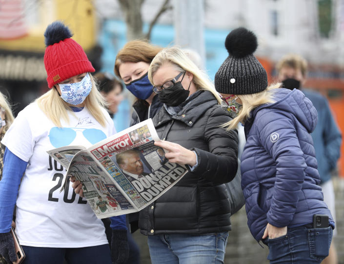 Residents read a copy of their local paper in the town of Ballina, North West of Ireland, the ancestral home of President elect Joe Biden, Saturday, Nov. 7, 2020. Biden was elected Saturday as the 46th president of the United States, defeating President Donald Trump in an election that played out against the backdrop of a pandemic, its economic fallout and a national reckoning on racism. (AP Photo/Peter Morrison)