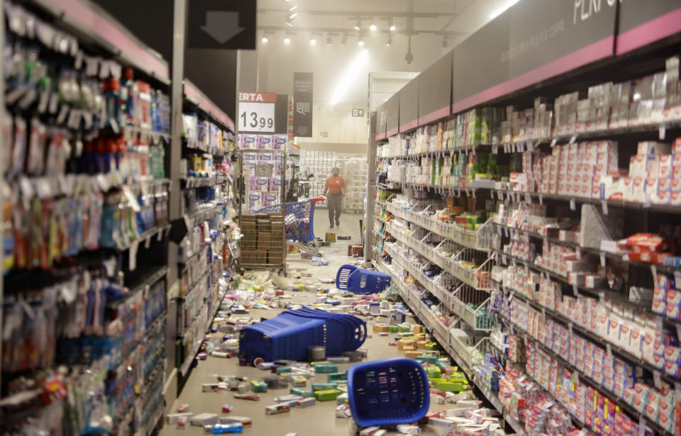 Products knocked off shelves by protesters litter an aisle at a Carrefour supermarket during a protest against the murder of Black man Joao Alberto Silveira Freitas at a different Carrefour supermarket the night before, on Brazil's National Black Consciousness Day in Sao Paulo, Brazil, Friday, Nov. 20, 2020. Freitas died after being beaten by supermarket security guards in the southern Brazilian city of Porto Alegre, sparking outrage as videos of the incident circulated on social media. (AP Photo/Andre Penner)