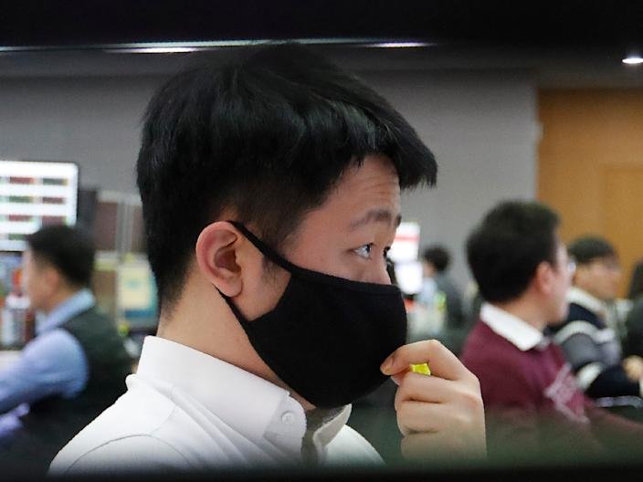 <br>A currency trader wearing a face mask watches monitors at KEB Hana Bank in Seoul on March 5.