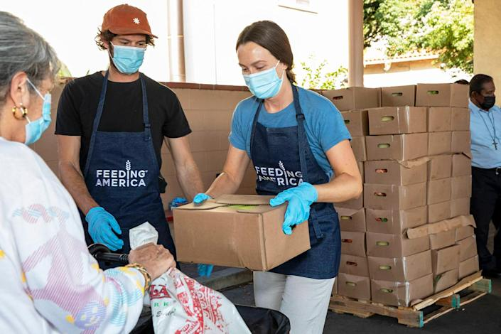 <p>Adam Brody and Leighton Meester hand out produce, beans, rice and other essential items while volunteering with Feeding America for a day of giving back at the Los Angeles Regional Food Bank.</p>