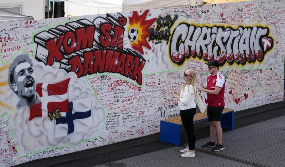 People leave well wishes at a graffiti for Danish player Christian Eriksen on a wall at the fanzone in Copenhagen, Denmark, Monday, June 14, 2021. (AP Photo/Martin Meissner)