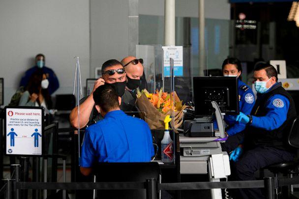 PHOTO: A passenger removes their face mask for an identification check at a Transportation Security Administration (TSA) checkpoint at Los Angeles International Airport in Los Angeles,  Nov. 18, 2020. (AFP via Getty Images)