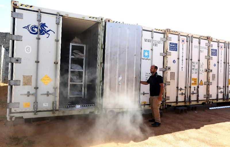 Ali Tuwaileb who is in charge of a high security complex in Misratah where the bodies of Islamic State (IS) group fighters are being stored opens one of the refrigerated containers at a make-shift morgue (AFP Photo/MAHMUD TURKIA)