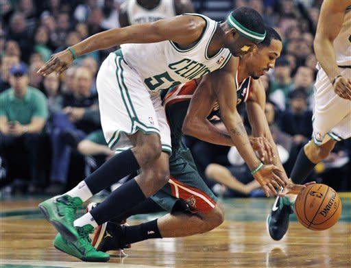 Boston Celtics point guard Keyon Dooling, left, and Milwaukee Bucks point guard Shaun Livingston (9) scramble for a loose ball during the first quarter of an NBA basketball game in Boston, Thursday, April 26, 2012. (AP Photo/Charles Krupa)