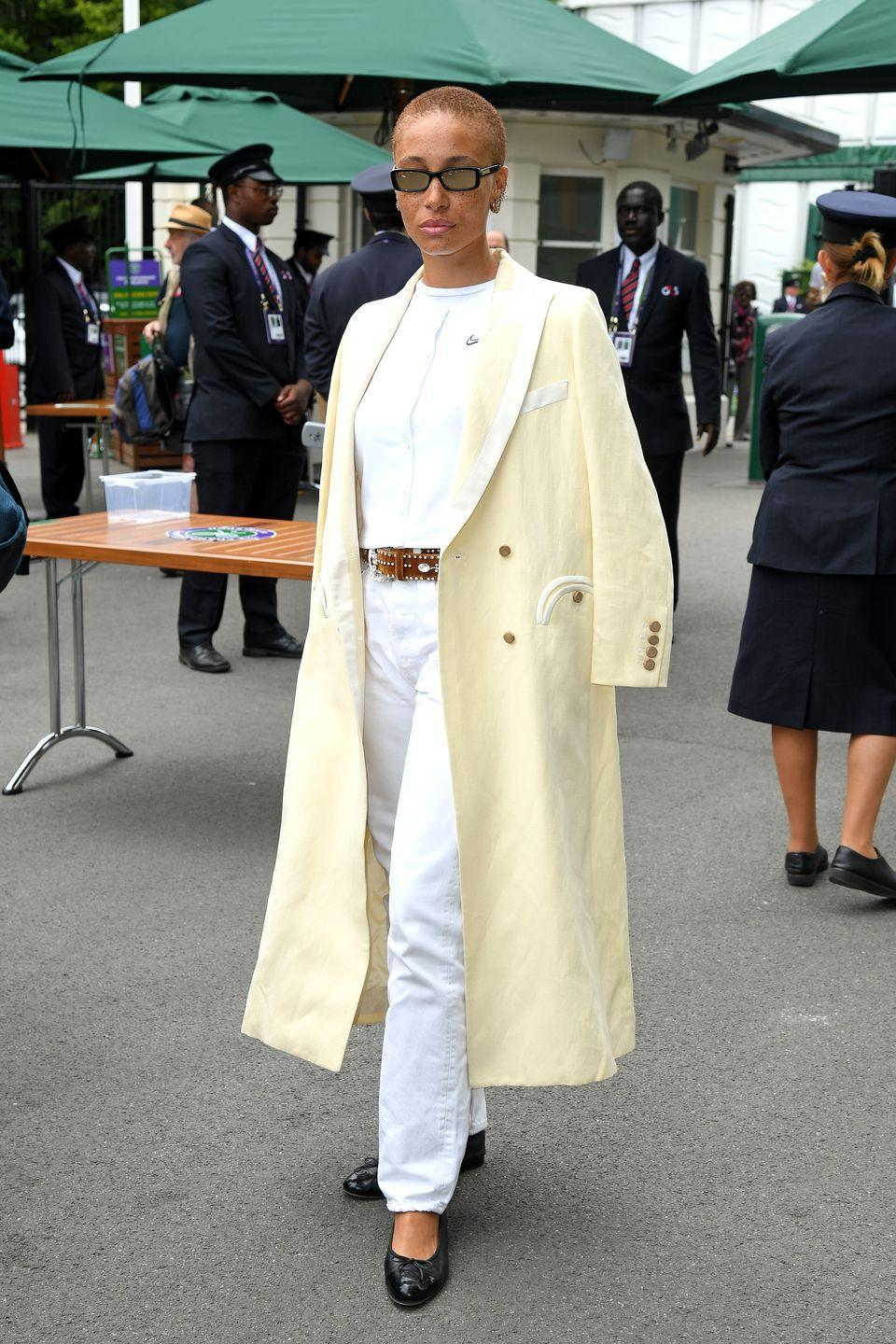 <p>The model and activist looked impeccably chic in a white top and jeans layered with a long cream coat for the tennis festivities.</p>