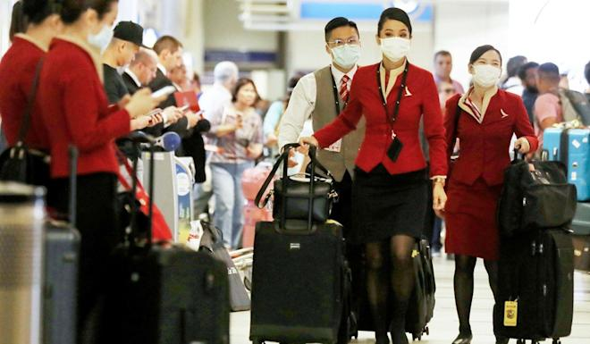 Flight crew from Cathay Pacific, wearing protective masks, walk through Los Angeles International Airport in California. Photo: AFP