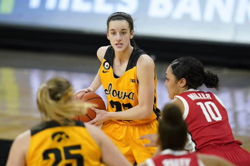 Iowa guard Caitlin Clark, center, looks to pass the ball during the first half of the team's NCAA college basketball game against Ohio State, Wednesday, Jan. 13, 2021, in Iowa City, Iowa. After Clark scored a career-high 37 points in the 92-79 win over Minnesota on January 6, Iowa coach Lisa Bluder said, I think, in her four-year career, Im going to run out of adjectives to describe her.(AP Photo/Charlie Neibergall)