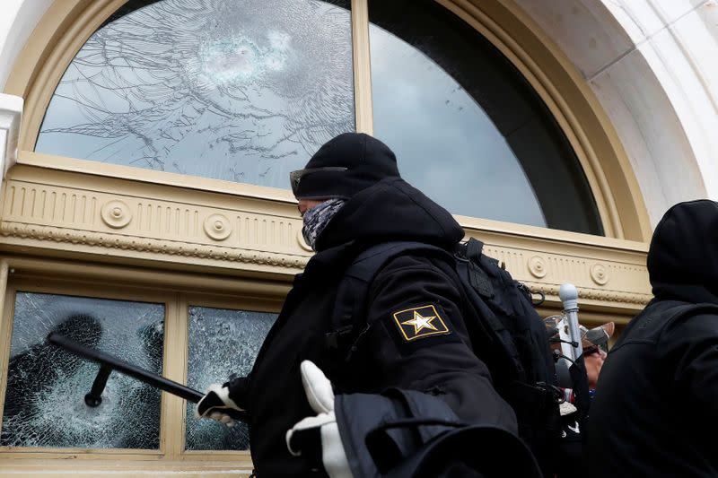 Pro-Trump protester smashes a window of the U.S. Capitol Building in Washington
