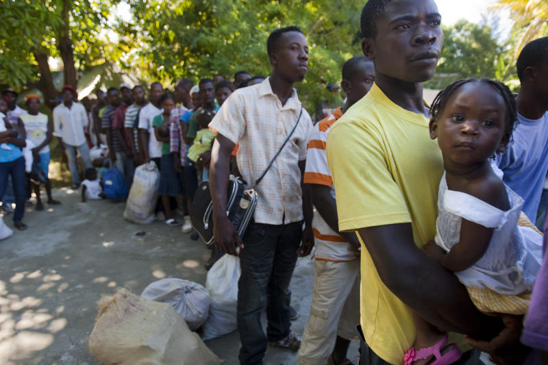 Louissien Pierra, 25, who was born in Neiba, Dominican Republic, holds his two-year-old daughter Anita Pierra as they wait to board a bus to a Haitian town where they have family, in Croix-des-Bouquets, Haiti, Monday, Nov. 25, 2013. Expulsions and voluntary departures from the DR to Haiti follow violence that engulfed the town of Neiba in the southwestern corner of the Dominican Republic. Relations between the two have soured since September when a Dominican court threatened to revoke citizenship for residents of the Dominican Republic of Haitian descent. (AP Photo/Dieu Nalio Chery)