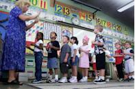 <p>A teacher lines up her kindergarteners to tour their new classroom.</p>