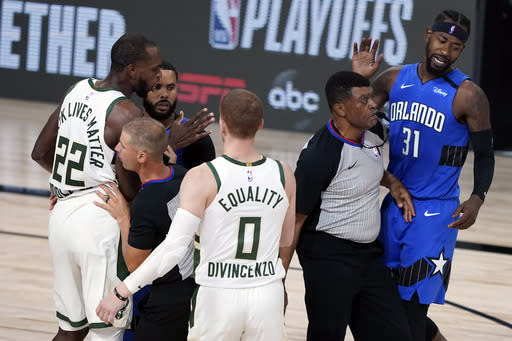 Officials separate Milwaukee Bucks' Khris Middleton (22) and Orlando Magic's Terrence Ross (31) after Ross fouled Middleton during the second half of an NBA basketball first round playoff game Saturday, Aug. 29, 2020, in Lake Buena Vista, Fla. Ross was called for a flagrant foul. (AP Photo/Ashley Landis)