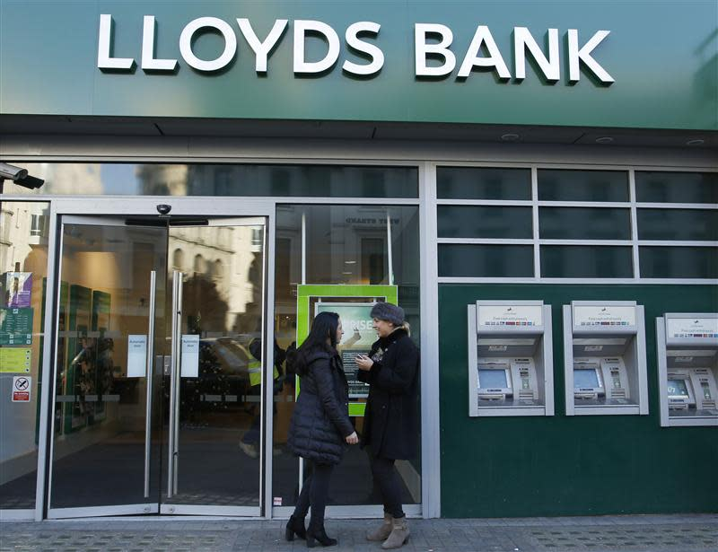 Two people stand outside a branch of Lloyds bank in central London