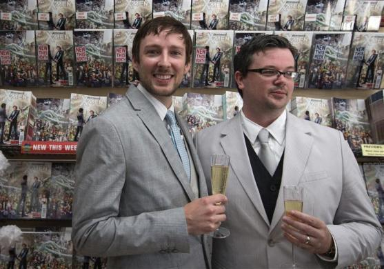 Jason Welker (L) and Scott Everhart hold their drinks in front of comic books after their wedding ceremony in Manhattan, New York June 20, 2012.