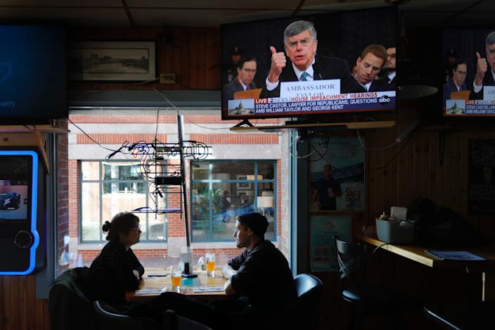 The televised impeachment hearings playing on monitors at the Commercial Street Pub, Wednesday, Nov. 13, 2019, in Portland, Maine.