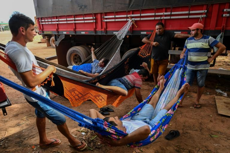 Brazilian trucker Erik Fransuer (L) speaks with other drivers resting on hammocks at a gas station in Ruropolis -- he spends at least 12 hours a day in his big rig