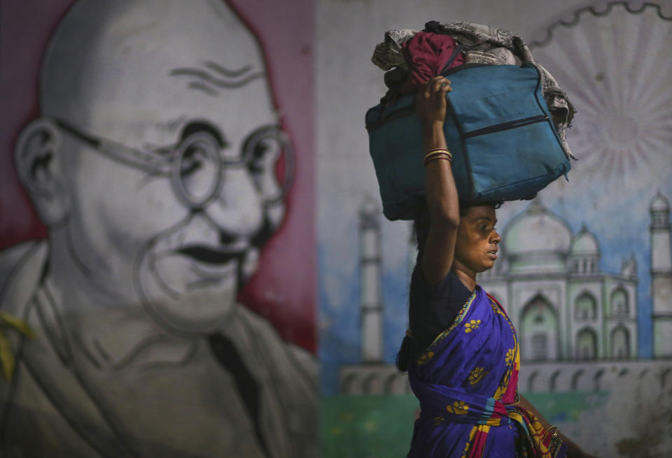 A migrant woman carries her belongings on her head as she walks past a wall painting of Mahatma Gandhi to board a train to her home state, at Hyderabad Railway Station in Hyderabad, India, Saturday, May 23, 2020. India's lockdown was imposed on March 25 and has been extended several times. On May 4, India eased lockdown rules and allowed migrant workers to travel back to their homes, a decision that has resulted in millions of people being on the move for the last two weeks. (AP Photo/Mahesh Kumar A.)