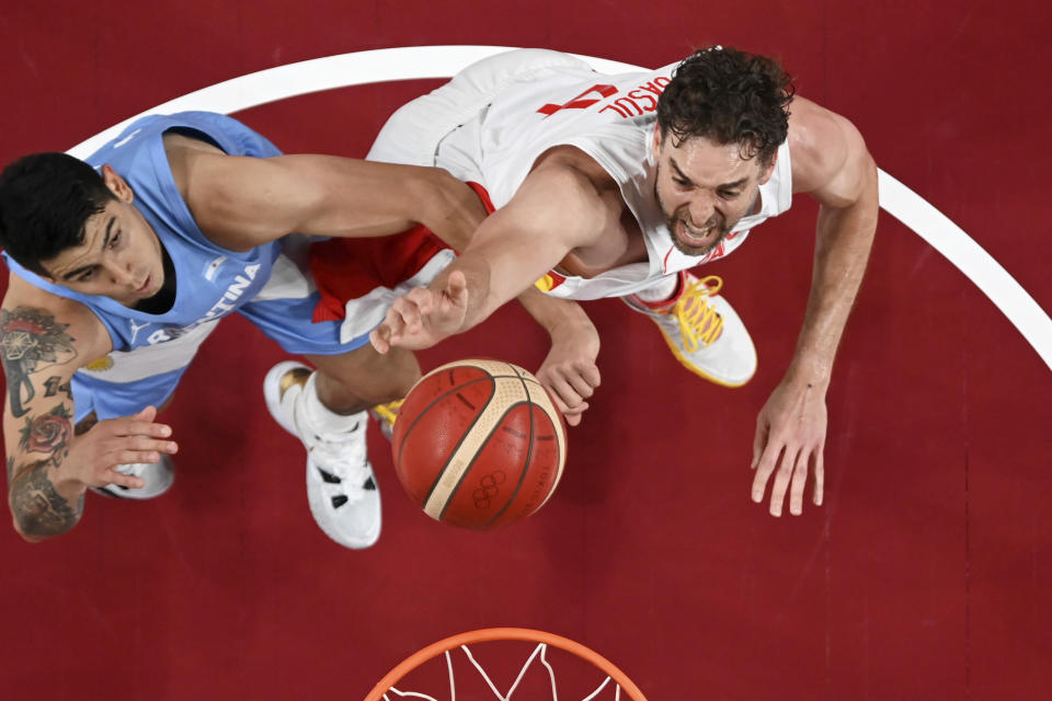 Argentina's Gabriel Deck, left, fights for a rebound with Spain's Pau Gasol during a men's basketball preliminary round game at the 2020 Summer Olympics, Thursday, July 29, 2021, in Saitama, Japan. (Aris Messinis/Pool Photo via AP)