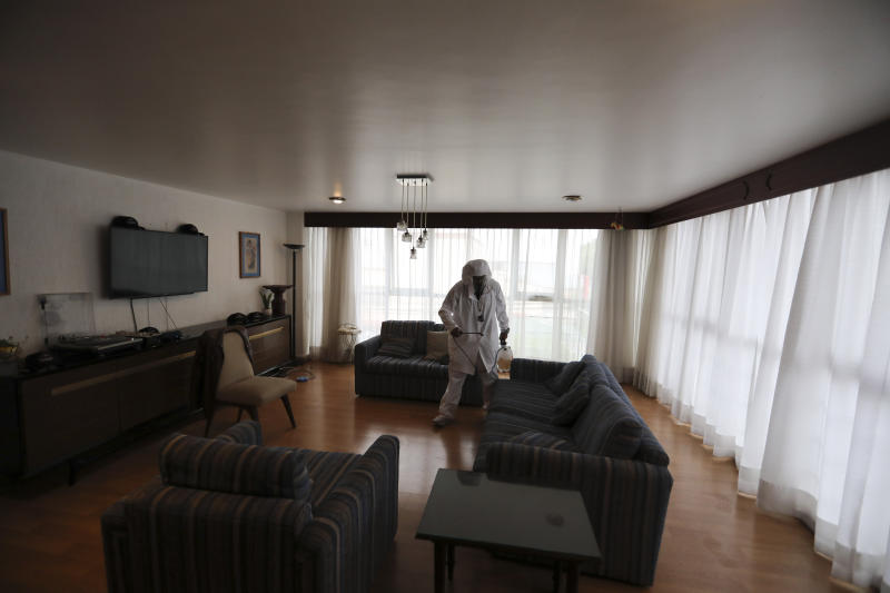 A worker sprays a living room with disinfectant in preparation for dancers performing in a client's home in Mexico City, Saturday, Aug. 8, 2020. The pandemic has forced business to adapt to a new normality and the adult entertainment industry is no exception. After three months of inactivity, Mi Ultimo Beso relaunched his table-dance-at-home service observing health measures. (AP Photo/Eduardo Verdugo)