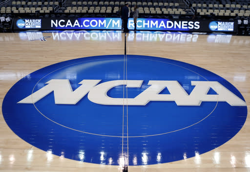 FILE - In this March 18, 2015, file photo, the NCAA logo is displayed at center court as work continues at The Consol Energy Center in Pittsburgh, for the NCAA college basketball tournament. A bill being introduced Thursday, Dec. 17, 2020, by four Democratic lawmakers would grant college athletes sweeping rights to compensation, including a share of the revenue generated by their sports, and create a federal commission on college athletics. The College Athletes Bill of Rights is sponsored by U.S. Senators Corey Booker (D-N.J.), Richard Blumenthal (D-Conn.) and Kirsten Gillibrand (D-N.Y.), and U.S. Rep. Jan Schakowsky (D-Ill.). If passed it could wreak havoc with the NCAA's ability to govern intercollegiate athletics, and the association's model for amateurism. (AP Photo/Keith Srakocic, File)