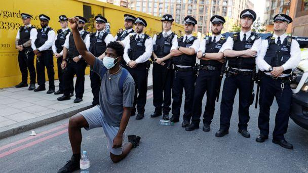 PHOTO: A man wearing a protective face mask kneels in front of police officers during a protest against the death in Minneapolis police custody of African-American man George Floyd near the U.S. Embassy, London, May 31, 2020. (John Sibley/Reuters)