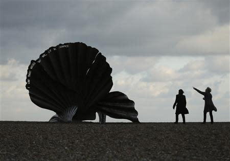 Women look at Scallop (2003) by sculptor Maggi Hambling, a tribute to composer Benjamin Britten, on Aldeburgh beach