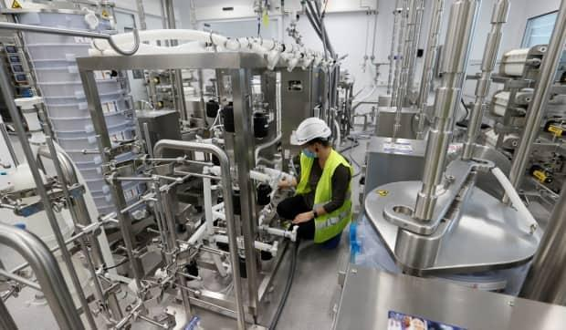 A staff member sets up an antibody production line at the Ibex building of Lonza, where the Moderna mRNA (COVID-19 vaccine is produced, in Visp, Switzerland, on Sept. 29, 2020. (Denis Balibouse/Reuters - image credit)