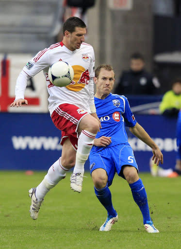New York Red Bulls' Kenny Cooper, left, plays the ball in front of Montreal Impact's Tyson Wahl, right, during the second half of an MLS soccer game in Harrison, N.J., Saturday, March 31, 2012.The Red Bulls won 5-2. (AP Photo/Mel Evans)