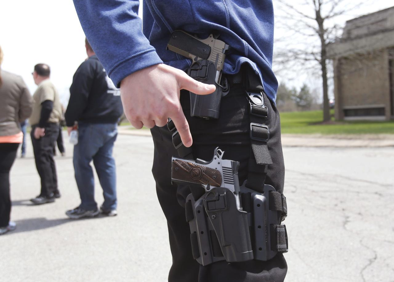 A gun rights supporter openly carries two pistols strapped to his leg during a rally in support of the Michigan Open Carry gun law in Romulus, Michigan April 27, 2014. REUTERS/Rebecca Cook (UNITED STATES - Tags: CIVIL UNREST POLITICS SOCIETY)