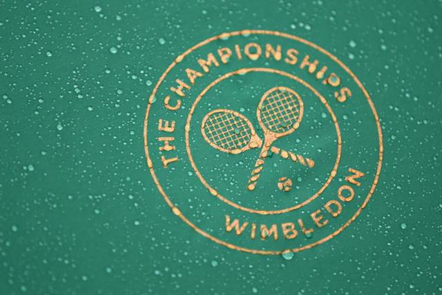 Raindrops fall on a Wimbledon umbrella as tennis fans huddle under umbrellas as they watch Roger Federer of Switzerland play Gilles Muller of Luxembourg on a a large TV screen at the All England Lawn Tennis Championships in Wimbledon, London, Thursday, June 26, 2014. (AP Photo/Ben Curtis)