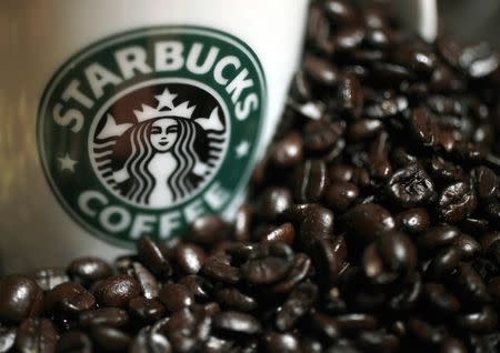 A mug bearing a Starbucks logo is pictured next to coffee beans during a news conference in Tokyo, in this file picture taken April 13, 2010.    REUTERS/Yuriko Nakao/Files