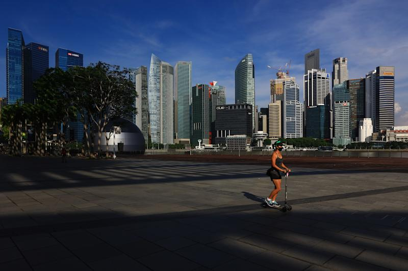 SINGAPORE - JUNE 07: A woman wearing a protective mask rides a skate scooter along the Marina Bay waterfront with the central business district seen in the background on June 7, 2020 in Singapore. From June 2, Singapore embarked on phase one of a three phase approach against the coronavirus (COVID-19) pandemic as it began to ease the partial lockdown measures by allowing the safe re-opening of economic activities which do not pose high risk of transmission. This include the resumption of selected health services, re-opening of schools with school children attending schools on rotational basis, manufacturing and production facilities, construction sites that adhere to safety measures, finance and information services that do not require interactions and places of worship, amongst others. Retail outlets, social and entertainment activities will remain closed and dining in at food and beverage outlets will still be disallowed. The government will further ease restriction by the middle of June if the infection rate within the community remains low over the next two weeks. (Photo by Suhaimi Abdullah/Getty Images)