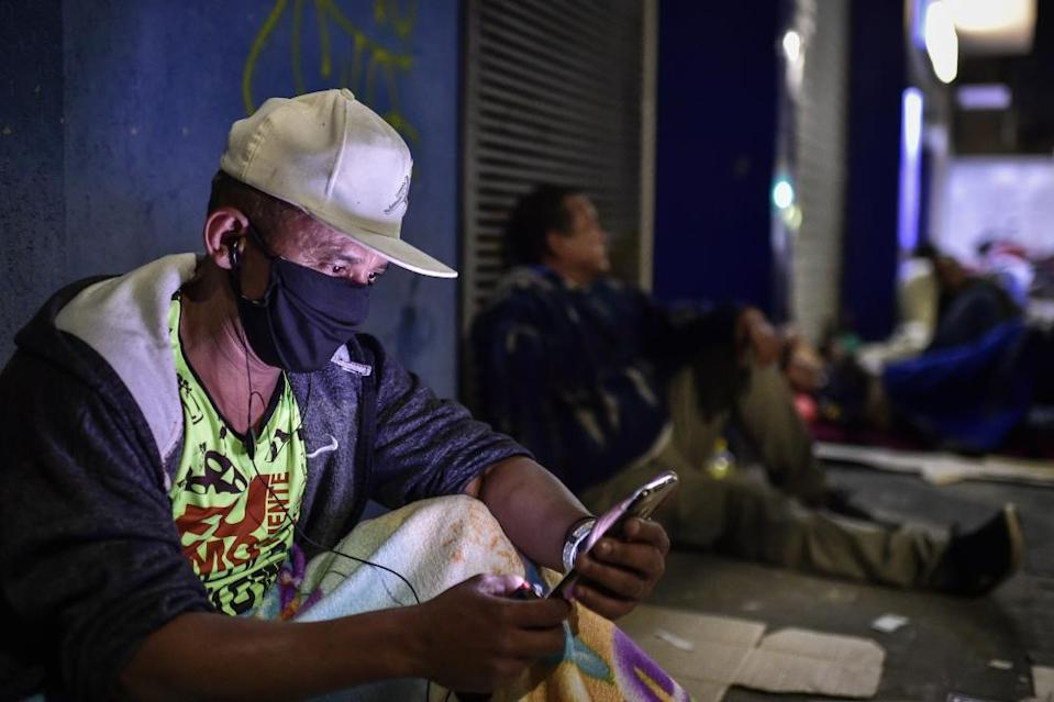 """<span class=""""element-image__caption"""">A man checks his phone outside a branch of Caixa Econômica Federal in Belo Horizonte.</span> <span class=""""element-image__credit"""">Photograph: Pedro Vilela/Getty Images</span>"""