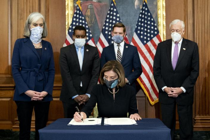 Pelosi signs a document with four people standing behind her, and American flags