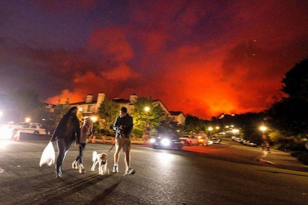 PHOTO: Residents walk a dog as a brush fire burns behind homes in the Pacific Palisades area of Los Angeles, May 15, 2021. (Ringo H.w. Chiu/AP)