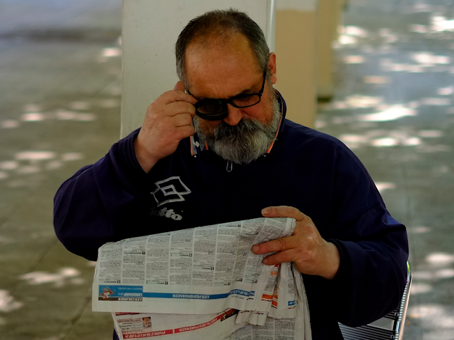 man reading newspaper magnifying glass
