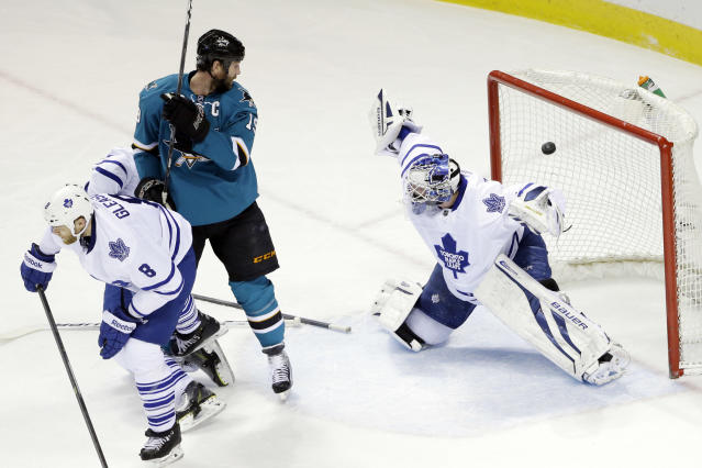 Toronto Maple Leafs goalie James Reimer, right, is beaten for a goal on a shot from San Jose Sharks' Brent Burns as Sharks center Joe Thornton, center, watches during the first period of an NHL hockey game on Tuesday, March 11, 2014, in San Jose, Calif. (AP Photo/Marcio Jose Sanchez)