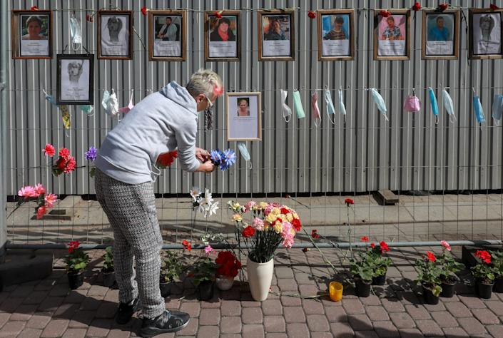 A St. Petersburg resident decorates a wall with flowers that was set up to honor the healthcare workers who died after contracting with the coronavirus.