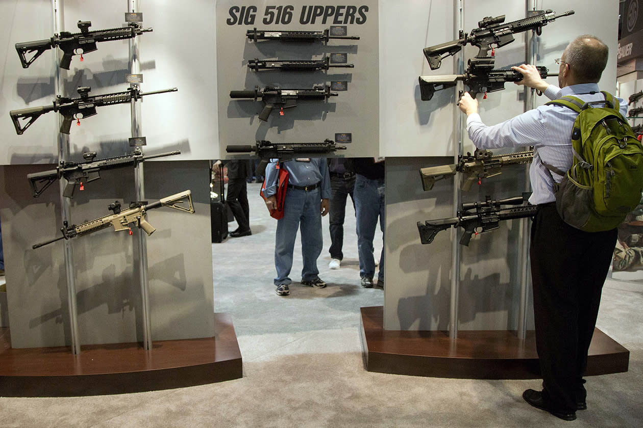 A convention attendee looks through a display of Sig Sauer semiautomatic rifles.