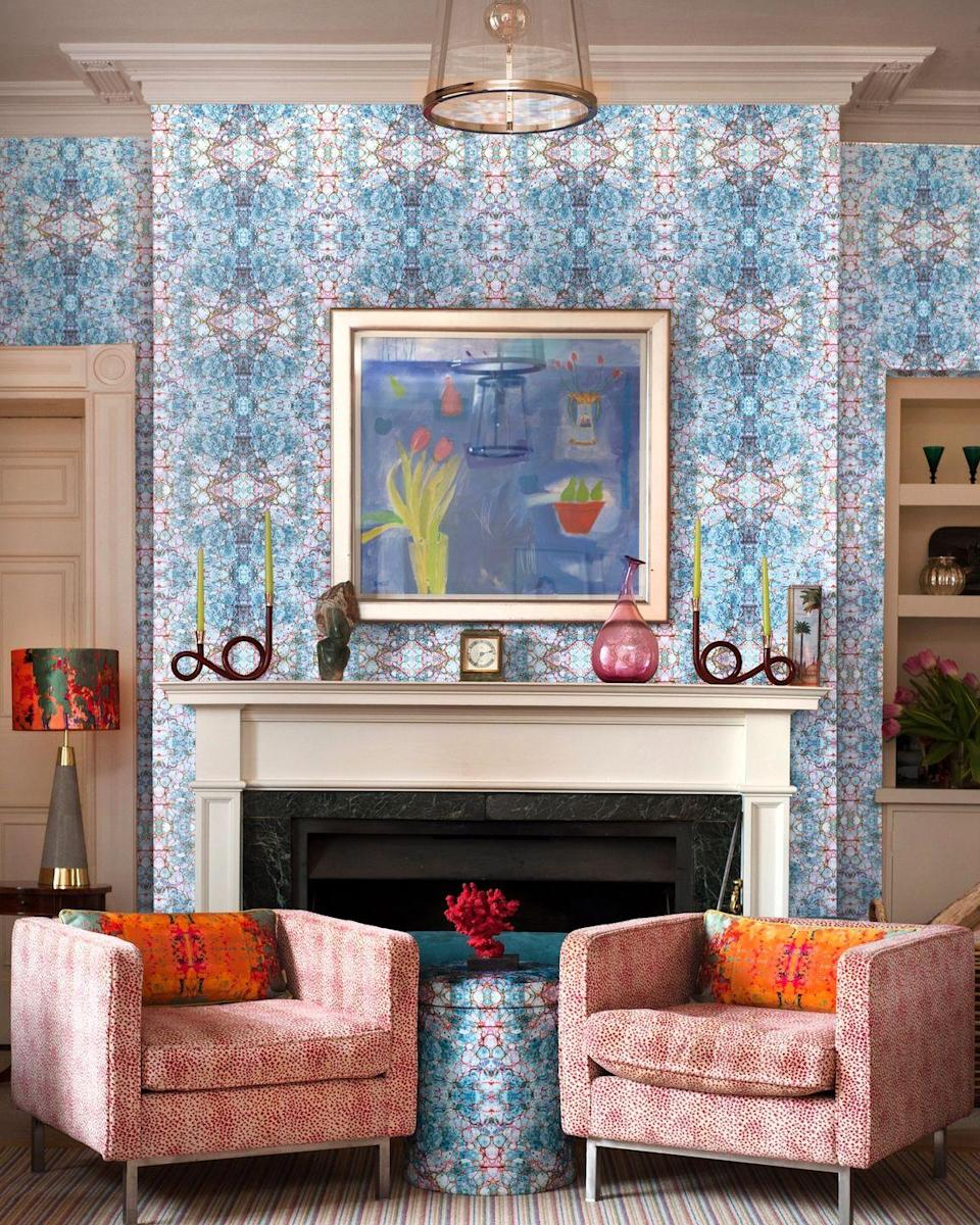 """<p>Susi Bellamy is renowned for her intricate designs with mirrored patterns taken from her original artwork and marbled papers. It's like looking through a kaleidoscope with all the different colours.</p><p>Because there are so many colours in it, it's easy to pull out shades for furniture and accessories as she has here with red, orange and pink.</p><p>'This paper would work well for a feature wall or inglenook in a modern apartment or retro style home,' says <a href=""""https://www.susi-bellamy.com/"""" rel=""""nofollow noopener"""" target=""""_blank"""" data-ylk=""""slk:Susi Bellamy"""" class=""""link rapid-noclick-resp"""">Susi Bellamy</a>, Wallpaper, Fabric and Accessory Designer. 'Perfect for dark corners to add some bold colour and pattern or behind a sideboard for some """"modern art for the wall"""".'</p><p>Pictured: Pietra Blue mica non-woven wallpaper; Grey Stucco kaleidoscope oblong velvet cushions; matching velvet shade; Pietra Blu velvet storage stool, all <a href=""""https://www.susi-bellamy.com/"""" rel=""""nofollow noopener"""" target=""""_blank"""" data-ylk=""""slk:Susi Bellamy"""" class=""""link rapid-noclick-resp"""">Susi Bellamy</a></p>"""