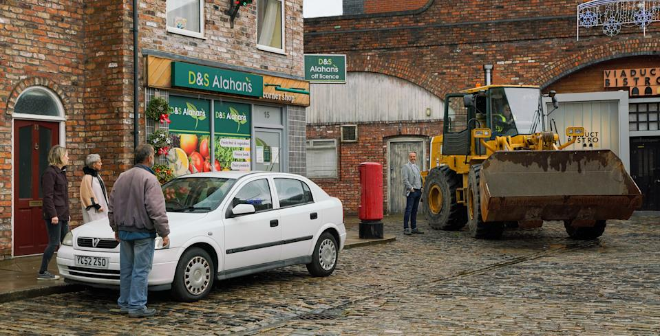 On the street, Abi Franklin, Kevin Webster, Debbie Webster, Brian, Cathy, David, Ken, Rita and Shona watch with horror as a bulldozer heads towards the brewery. (ITV)