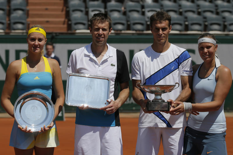 Lucie Hradecka, right, and Frantisek Cermak, second right, of the Czech Republic hold the trophy after winning the mixed doubles match 1-6, 6-4, 10-6, against Kristina Mladenovic of France, left, and Daniel Nestor of Canada, second left, at the French Open tennis tournament, at Roland Garros stadium in Paris, Thursday June 6, 2013. (AP Photo/Petr David Josek)