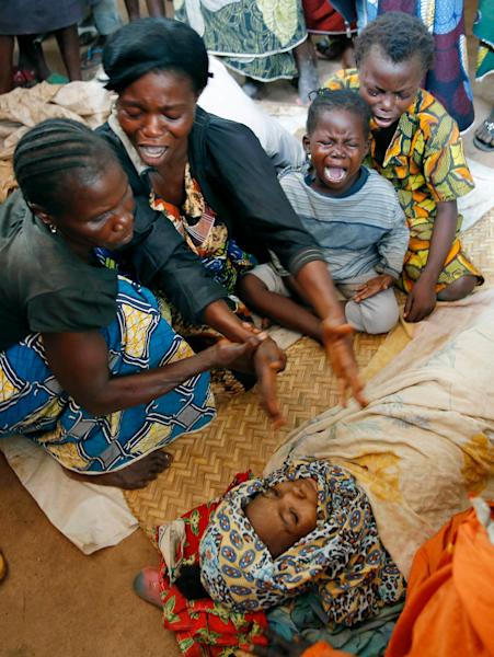 Diane Seresona, second left, is overwhelmed by grief as she sees the body of Prudence Seresona, 27, who just passed away from Malaria at the makeshift camp for internally displaced people set up in the airport in Bangui, Central African Republic, Friday Dec. 13, 2013. Over 30,000 are believed to seek refuge around the airport. Elsewhere in town, French troops backed by an helicopter traded fire with unidentified assailants as France's Defense Minister Jean-Yves Le Drian arrived in Bangui. More than 500 people have been killed over the past eight days in sectarian fighting in Central African Republic. (AP Photo/Jerome Delay)