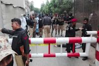 Police secure an area around a body outside the stock exchange -- Karachi was once a hotspot for crime and violence