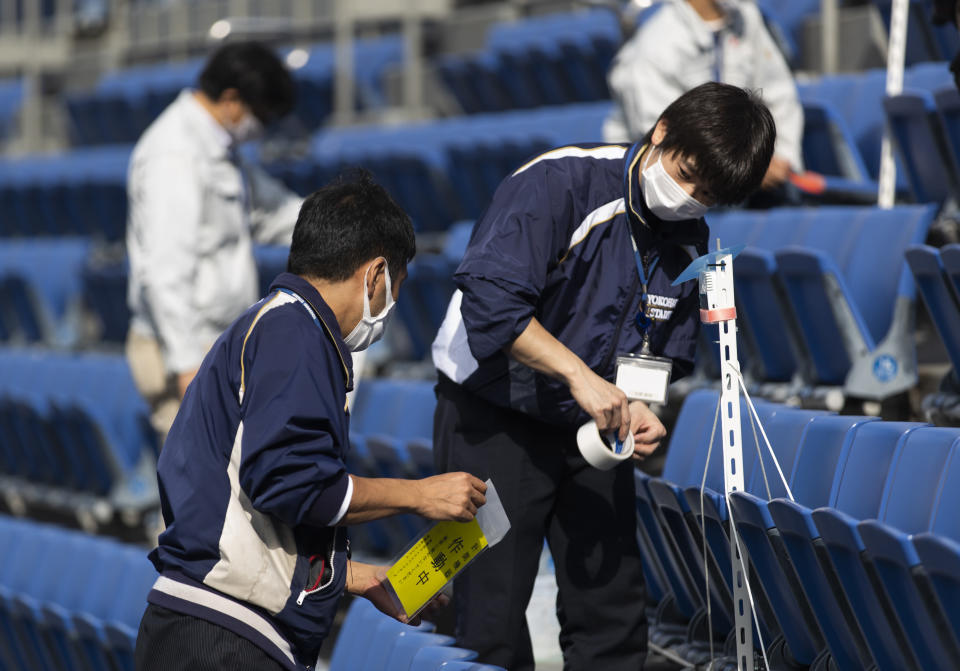 Stadium crew members install a device to detect carbon dioxide in the seats of a baseball stadium, home for the Yokohama DeNA BayStars, in Yokohama, south of Tokyo on Friday, Oct. 30, 2020. The device was introduced during a media tour before a Japanese professional baseball league game between the Hanshin Tigers and the DeNA BayStars on Friday. (AP Photo/Hiro Komae)