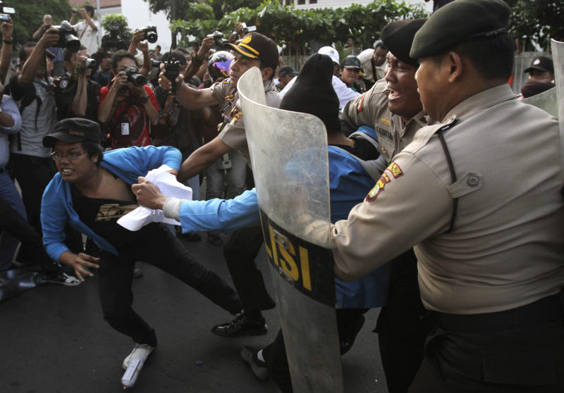 Indonesian police officers try to catch students during a protest against price hikes on fuel, in Jakarta, Indonesia, Wednesday, March 14, 2012 .(AP Photo/Achmad Ibrahim)