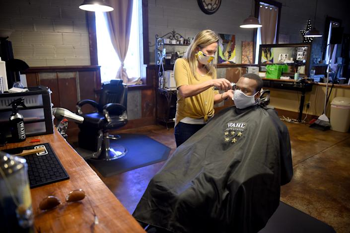 After opening following the coronavirus pandemic, Shelley Craft, owner of The Men's Refinery BarberSpa gives a haircut to Kenneth Gregory at her salon in Augusta, Ga., Friday morning April 23, 2020.