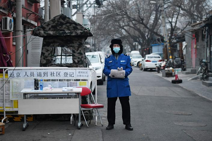 A security guard wears a facemask to protect against the COVID-19 coronavirus as he stands guard at a checkpoint at the entrance to an alley in Beijing on February 20, 2020. (Greg Baker/AFP via Getty Images)