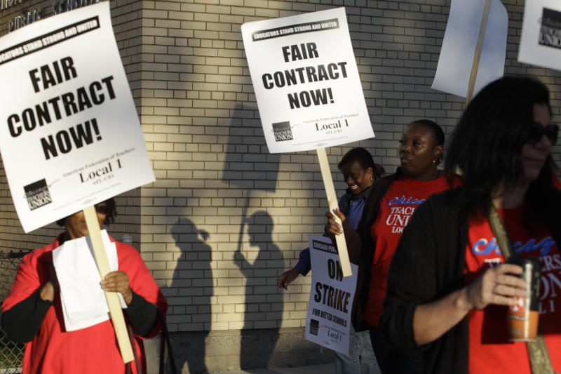 FILE - This Sept. 10, 2012 file photo shows Chicago teachers walk walking a picket line outside a school in Chicago, after they went on strike for the first time in 25 years. Teachers in Chicago, the nation's third-largest school district, again are inching closer to a strike that could take place as early as next month. AP Photo/M. Spencer Green, File)