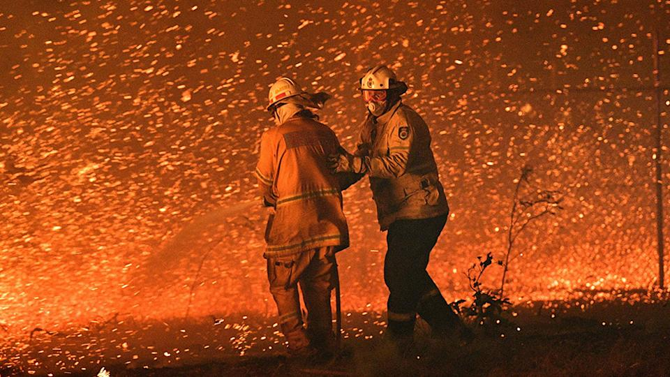 December 31, 2019 firefighters struggling against the strong wind in an effort to secure nearby houses from bushfires near the town of Nowra